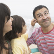 Hispanic boy touching father's ear — Stock Photo