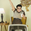Nerdy Asian man cheering in front of television — Stock Photo