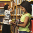 African American girl reading library book — Stockfoto