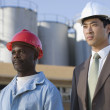 Multi-ethnic businessman and construction worker wearing hardhats — Stock Photo