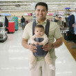 Hispanic father and baby in department store — Stock Photo