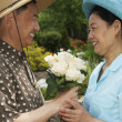 Senior Asian man giving flowers to wife — Stock Photo