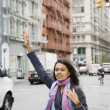 Mixed Race woman hailing taxi cab — Stock Photo