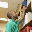 African American boy taking book off library shelf — Stock Photo