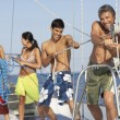Multi-ethnic friends pulling rope on sailboat — Stock Photo #23324178