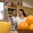 Multi-ethnic couple making orange juice — Stock Photo