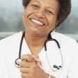 African American female doctor with hands clasped — Stock Photo