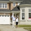 Pregnant Asian couple in front of new house — Stock Photo