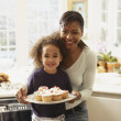 African mother and daughter with tray of cupcakes — Stock Photo #23324292