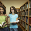 Multi-ethnic girls holding library books — Stok fotoğraf