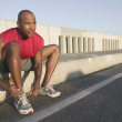 AfricAmericmale runner tying sneaker — Stock Photo #23324320