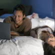 Asian couple relaxing on bed — Stock Photo
