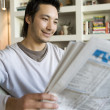 Asian man reading newspaper — Stock Photo