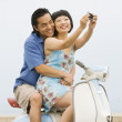 Stock Photo: Asian couple taking own photograph