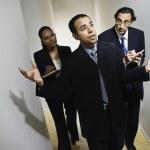 Multi-ethnic businesspeople walking in hallway — Stock Photo #23324412