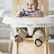 Asian baby sitting in highchair — Stock Photo