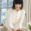 Asian woman putting strawberries on table — Stock Photo #23324458