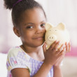 African American girl holding piggybank — Stock Photo