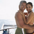 Multi-ethnic couple hugging on boat — Stock Photo