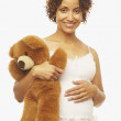 Pregnant Mixed Race woman holding teddy bear — Stock Photo