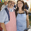 Hispanic couple wearing aprons at barbecue — Stock Photo