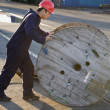 Asian male manual worker pushing wooden spool — Stock Photo #23324528
