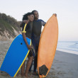 African couple holding surfboard and boogie board — Stock Photo