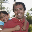 Hispanic father giving daughter piggy back ride — Stock Photo