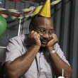 Senior African American male worker staring at birthday cupcake — Stock Photo