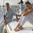 Multi-ethnic couple sitting on sailboat — Stock Photo