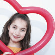 Hispanic girl holding heart-shaped balloon — Stock Photo