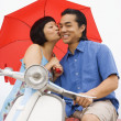 Asian woman kissing boyfriend on cheek — Stock Photo