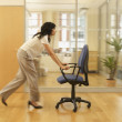 Stock Photo: Hispanic businesswompushing office chair