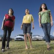Multi-ethnic women in front of low rider cars — Stock Photo