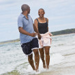 Senior African American couple running at beach — Foto Stock