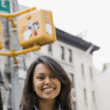 Mixed Race woman under street sign — Stock Photo