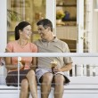 Multi-ethnic couple sitting on porch swing — Stock Photo