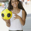 Mixed Race teenaged girl holding soccer ball — Stock Photo #23325430