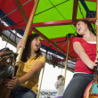 Mixed Race teenaged girls on carousel horse — Stock Photo