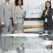 Multi-ethnic businesspeople next to graph — Stock Photo