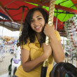 Mixed Race teenaged girl on carousel horse — Stock Photo