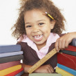 Mixed Race girl with stacks of books — Stock Photo