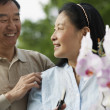 Senior Asian couple pruning flowers — Stock Photo