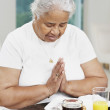 Senior African American woman saying grace — Foto de Stock
