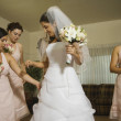 Hispanic bride and bridesmaids looking at dress — Stock Photo