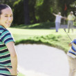Asian woman on golf course — Stock Photo
