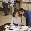 Multi-ethnic couple looking at flooring samples — ストック写真