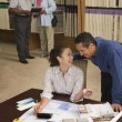 Multi-ethnic couple looking at flooring samples — Foto Stock