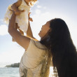 Pacific Islander mother holding daughter in air — Stock Photo