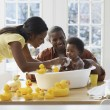 African parents bathing baby — Stock Photo